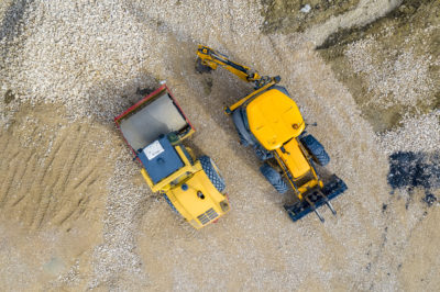 stunning aerial view of the stopped yellow excavator and drum roller at a construction site
